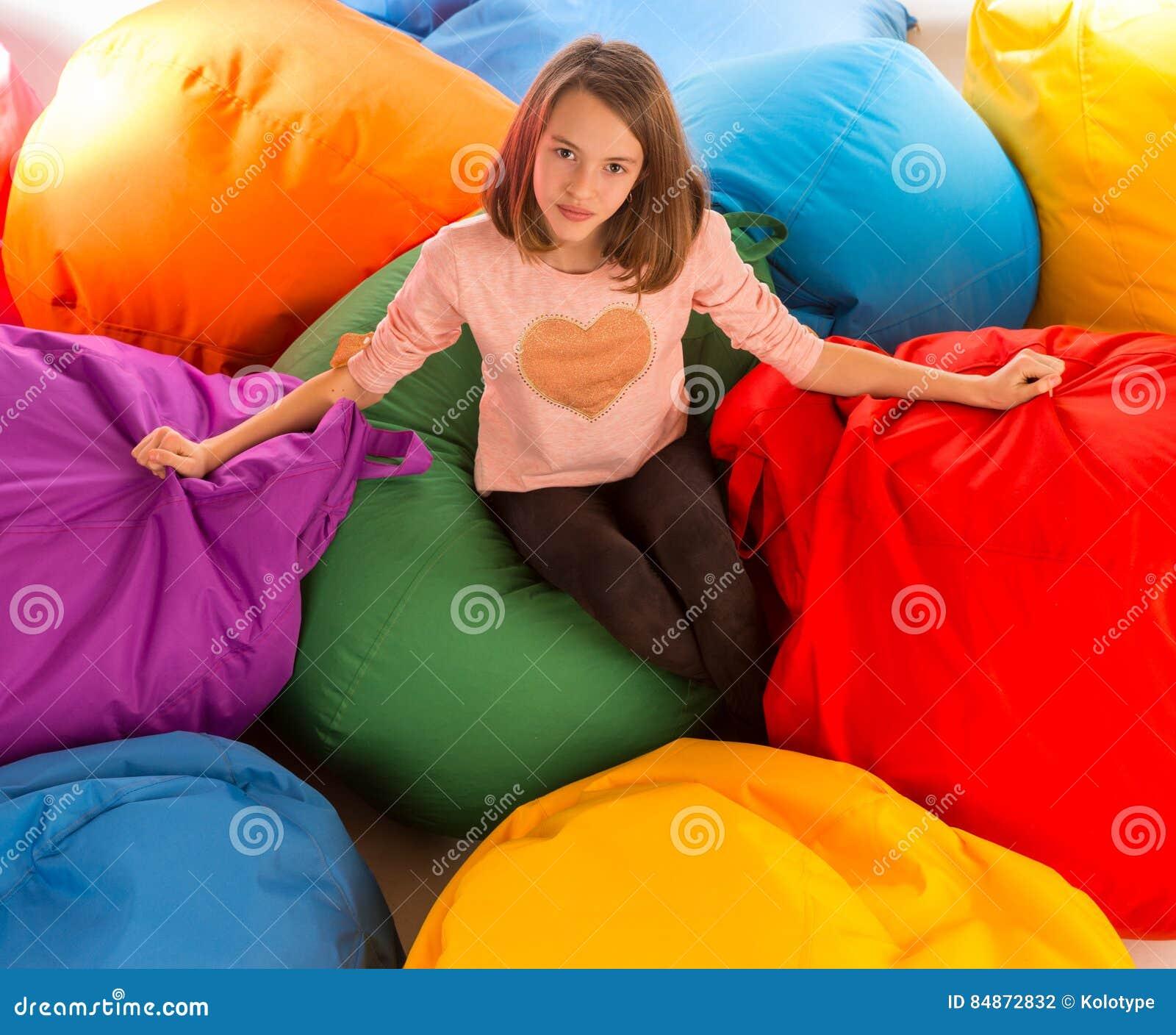坐在装豆子小布袋椅子之间的年轻愉快的女孩