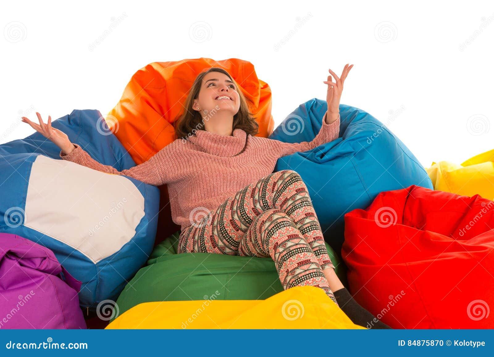 坐在装豆子小布袋椅子之间的年轻愉快的微笑的妇女