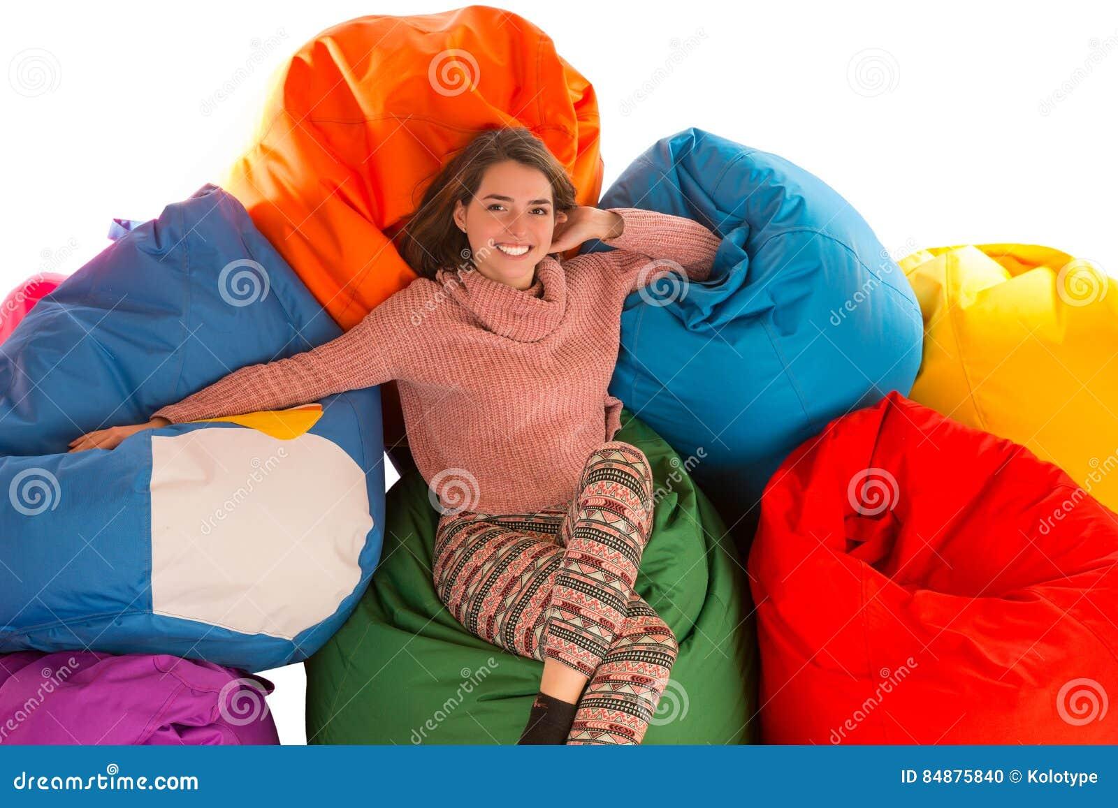 坐在装豆子小布袋椅子之间的年轻逗人喜爱的妇女