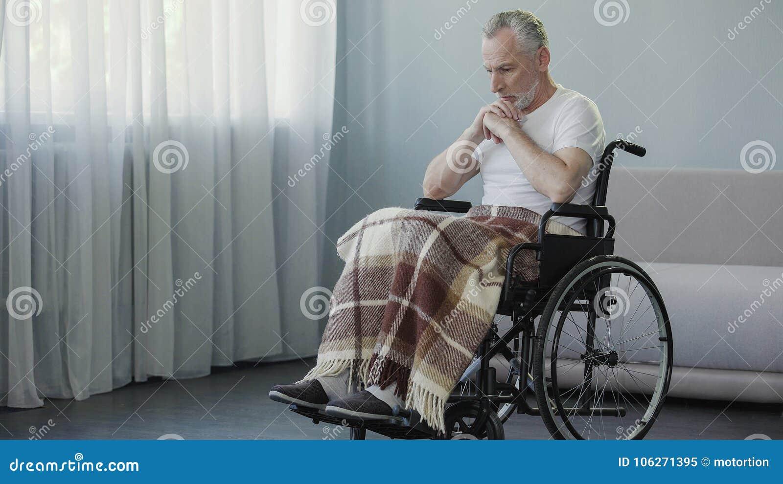 坐在轮椅和考虑生活,消沉的残疾人