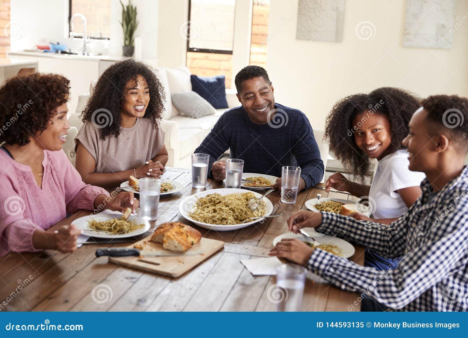 坐在饭桌吃与他们的孩子,关闭上的中间年迈的非裔美国人的夫妇