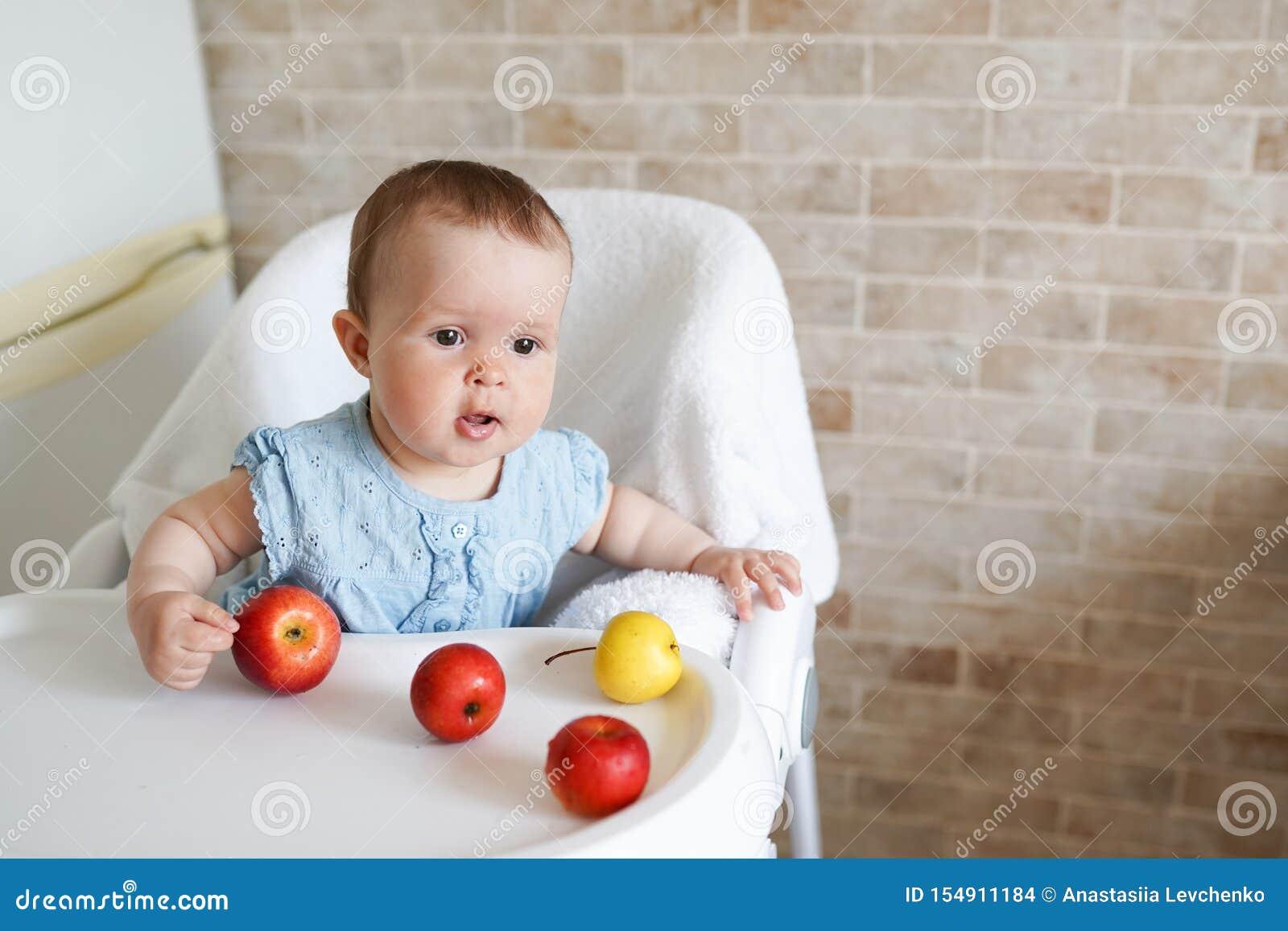 坐在高脚椅子的逗人喜爱的可爱的微笑的笑的白种人儿童孩子女孩画象吃苹果果子 每天生活方式