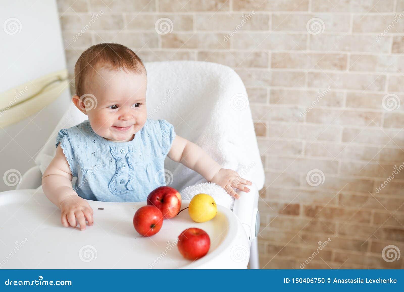 坐在高脚椅子的逗人喜爱的可爱的微笑的笑的白种人儿童孩子女孩画象吃苹果果子