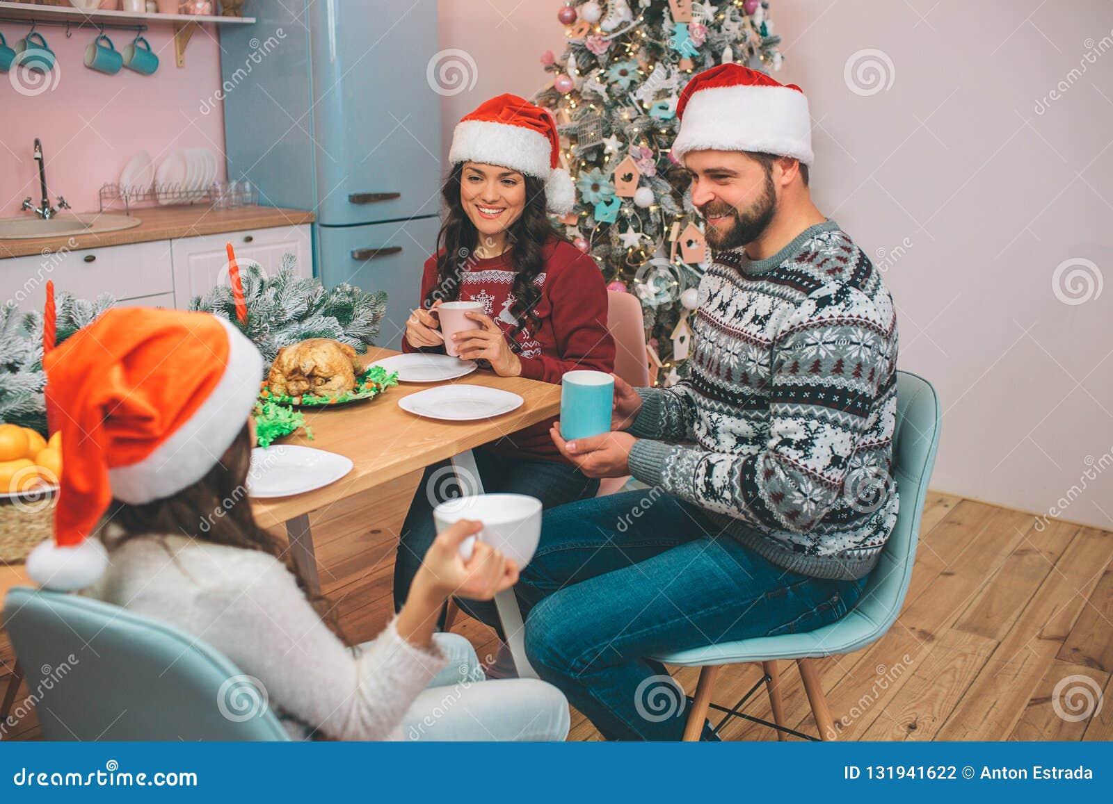 坐在tabel和神色的美丽的家庭的图片在彼此 他们在手上拿着杯子 人们互相微笑