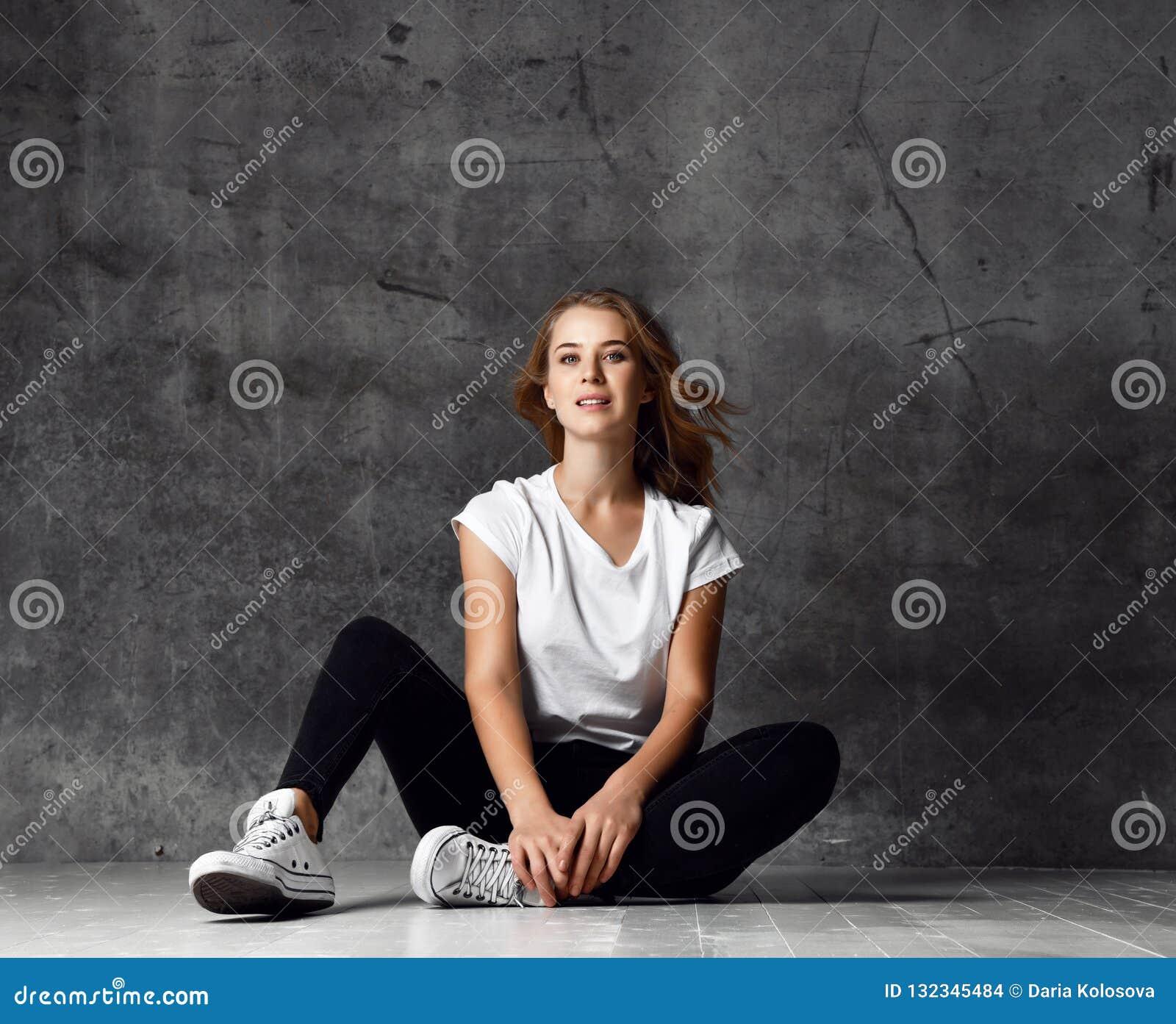 坐地板和看照相机的年轻白肤金发的女孩