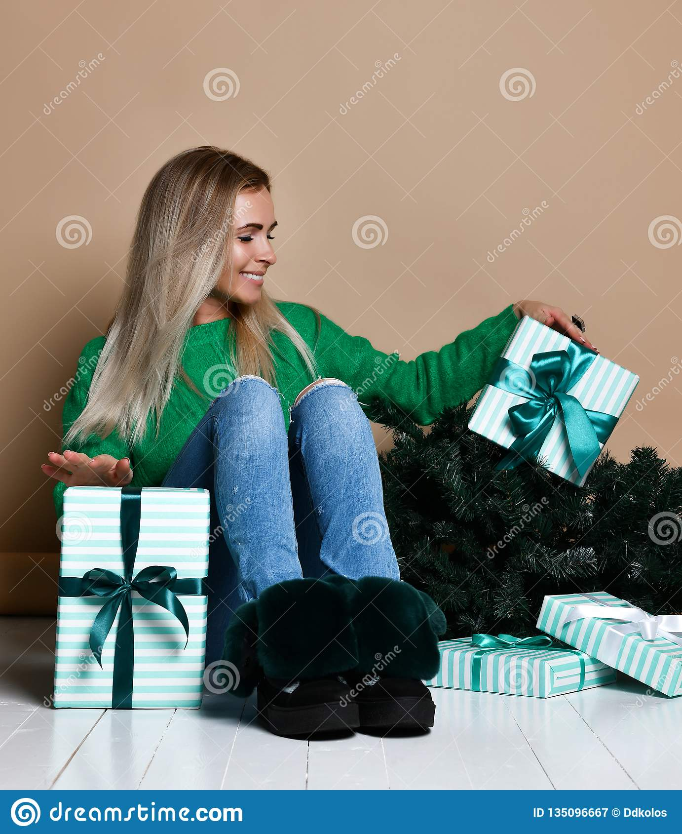 坐地板在冷杉圣诞树附近和作梦关于礼物、未来,礼物和等待的年轻女人奇迹