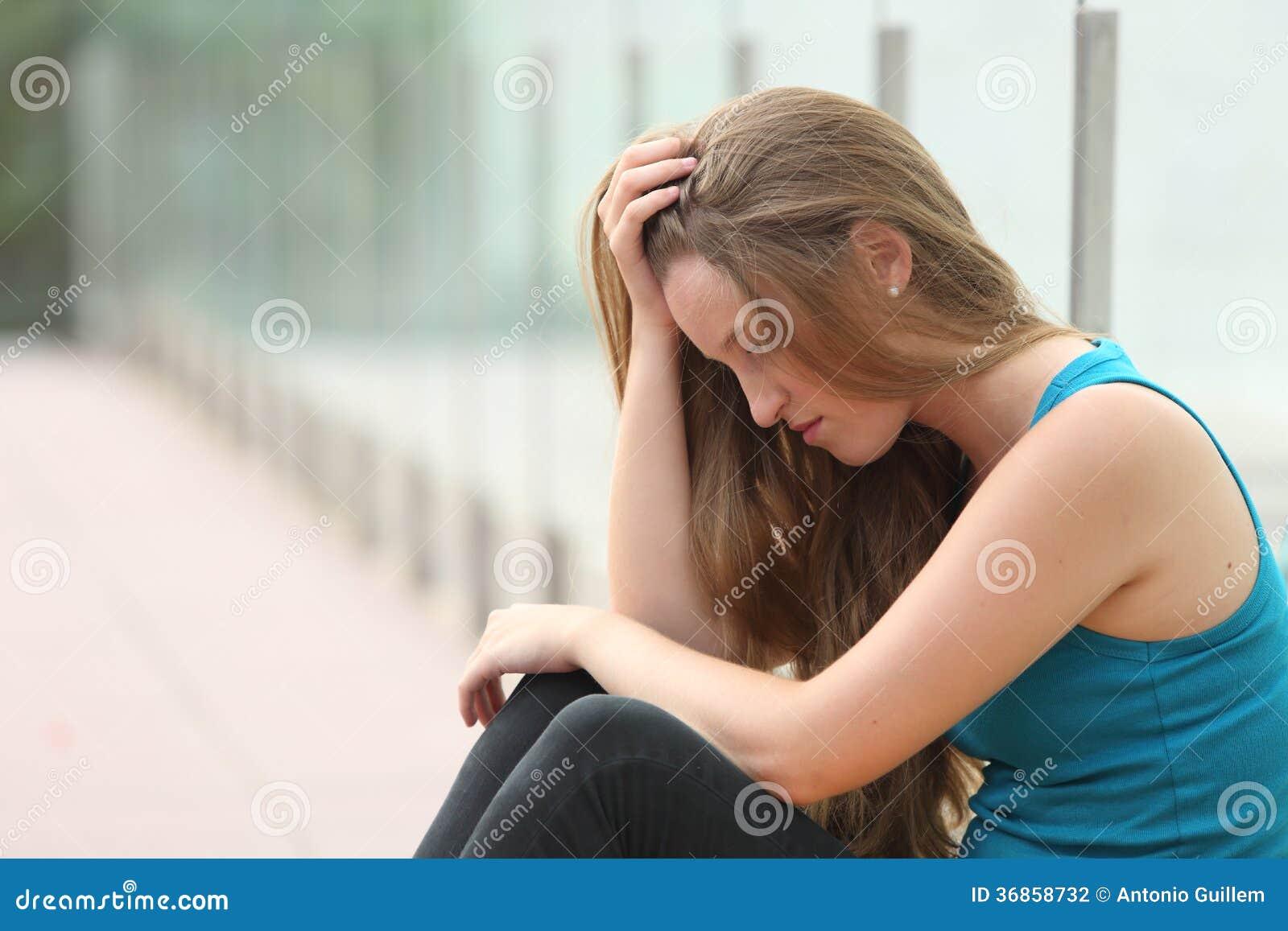 坐室外沮丧的少年女孩