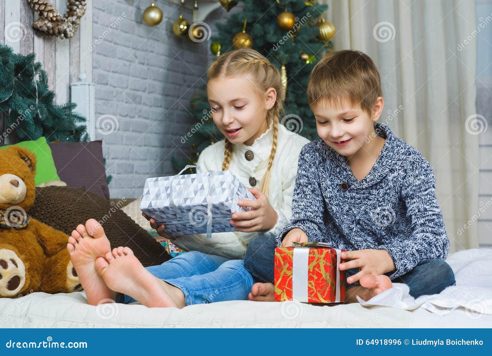 坐床和拿着礼物的愉快的孩子