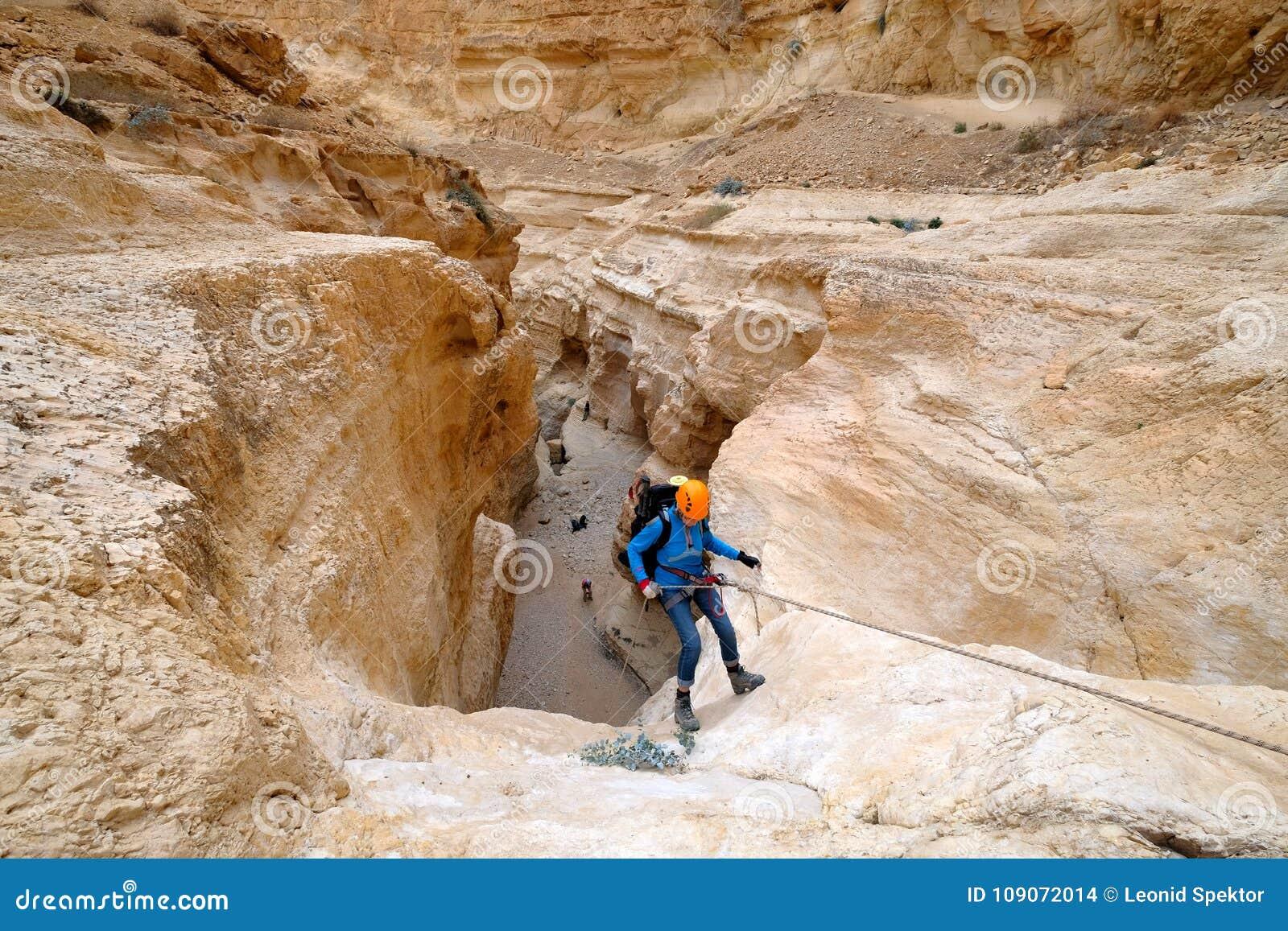 坐式下降法从干燥瀑布的登山人