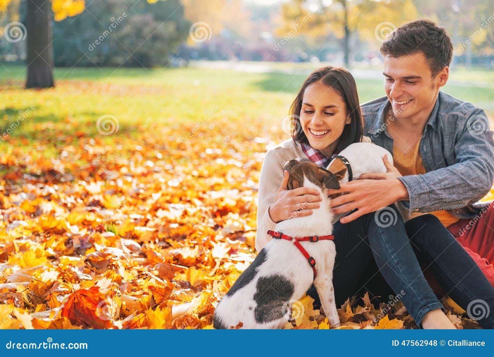 坐户外在秋天公园的愉快的年轻夫妇画象