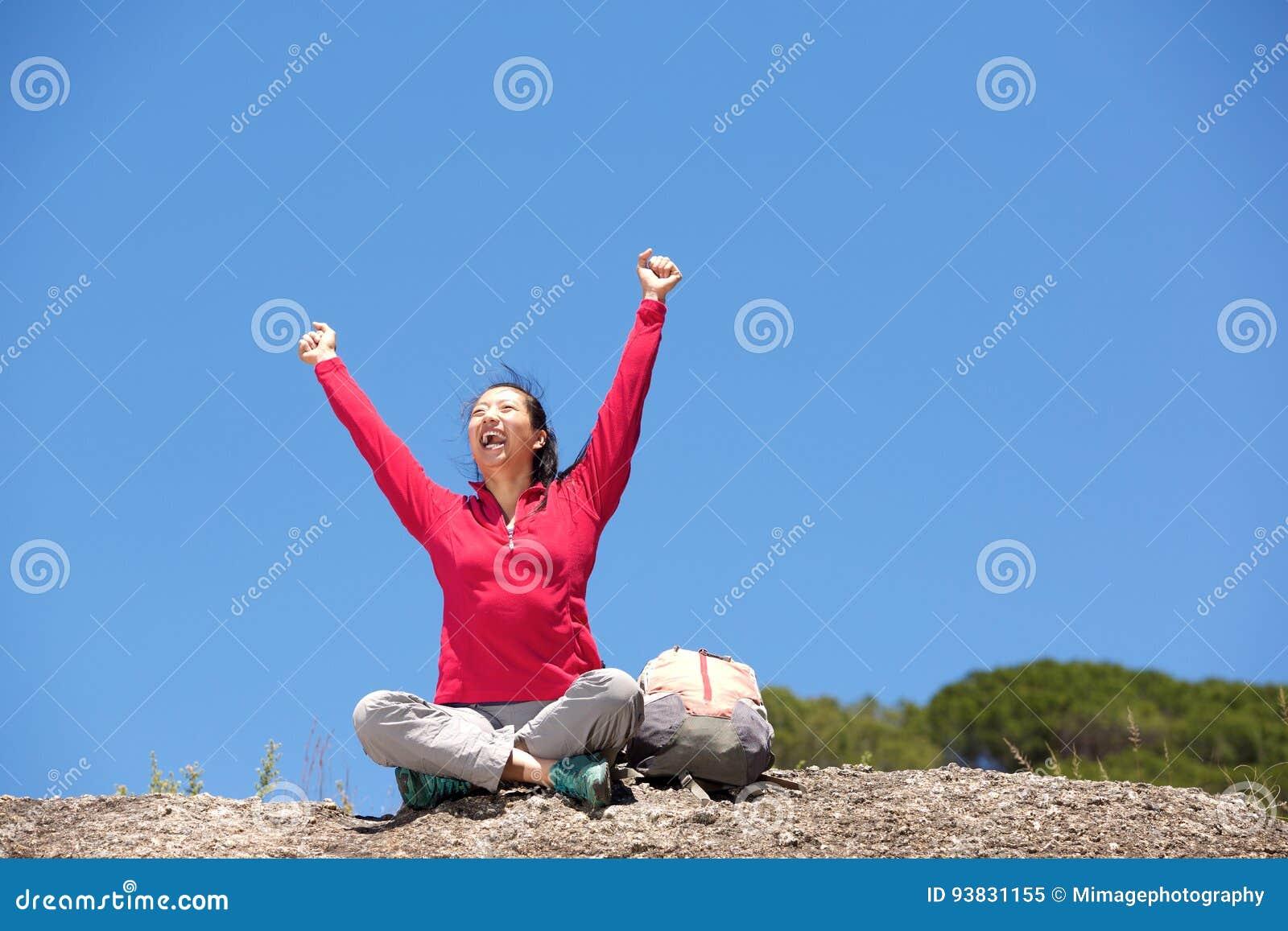 坐户外用手的亚裔女性远足者被举