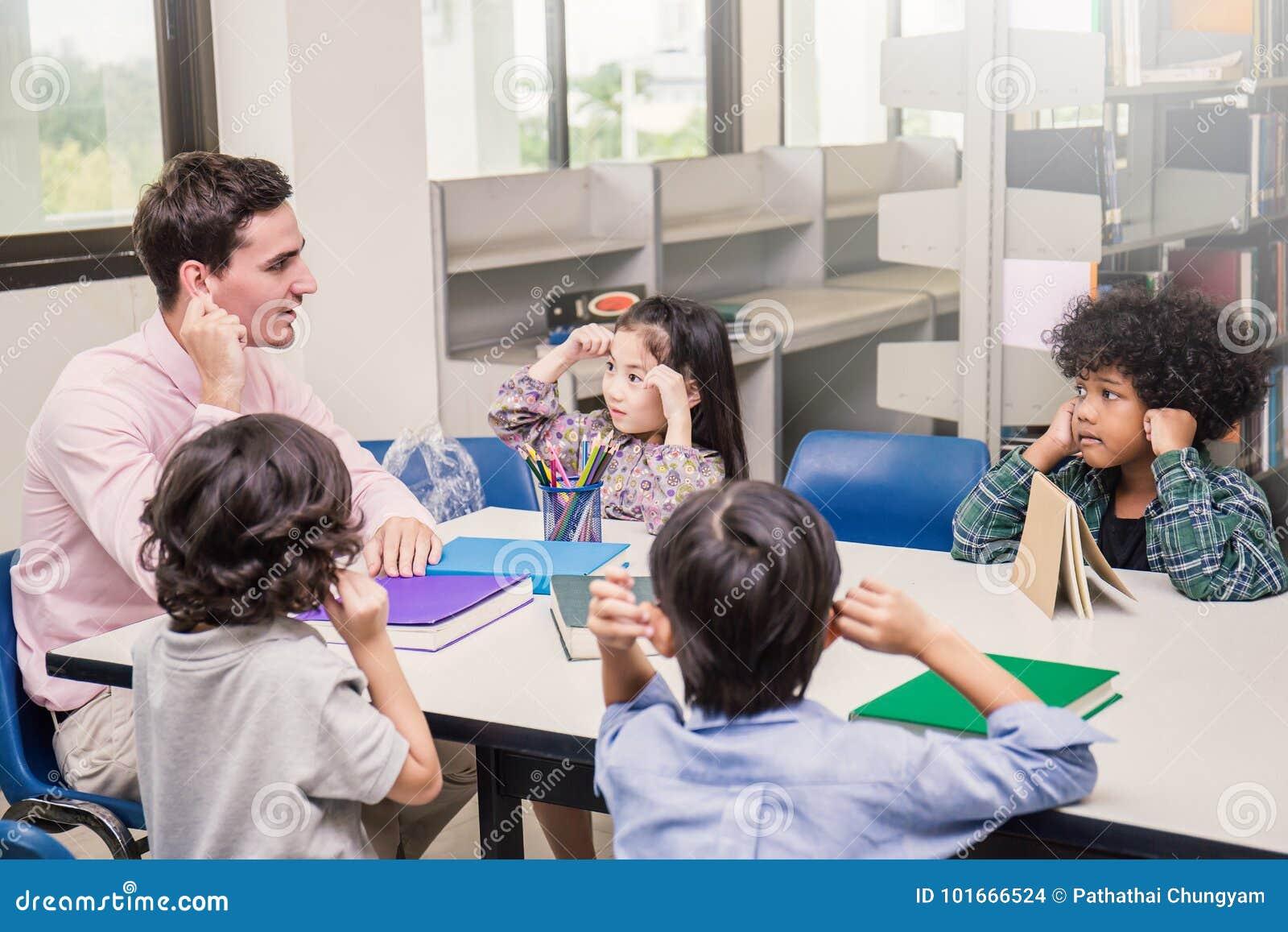 坐手的老师和小孩接触他们的耳朵