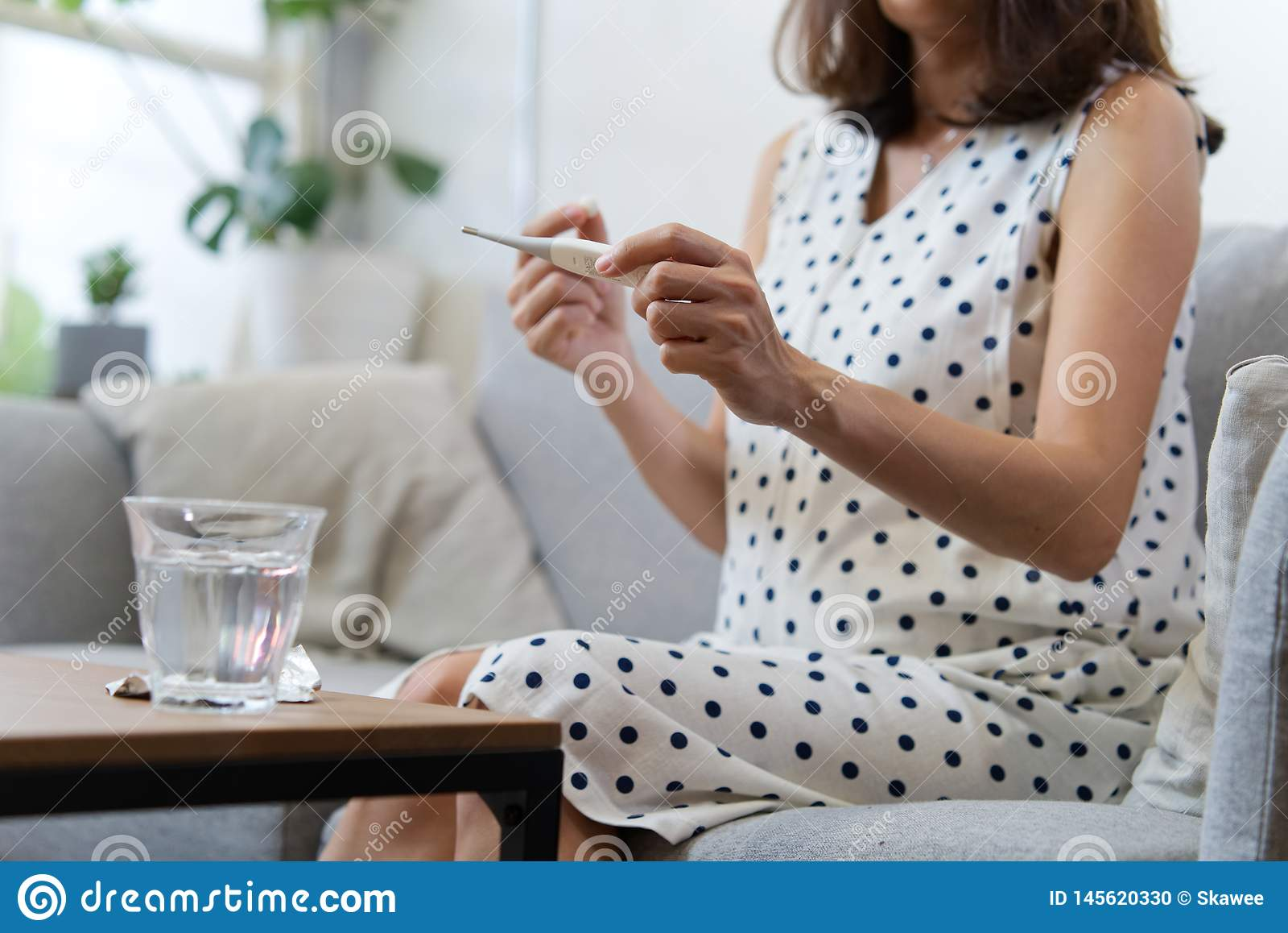 坐沙发在左手的藏品温度计和钻孔医学的亚裔孕妇在右手