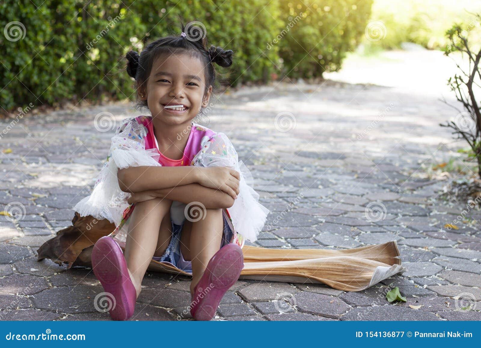 坐的女孩在公园愉快地吃棒棒糖