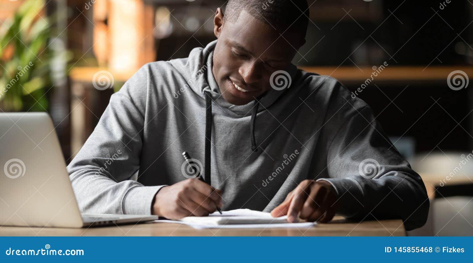 坐被聚焦的非洲的学生户内写在笔记本