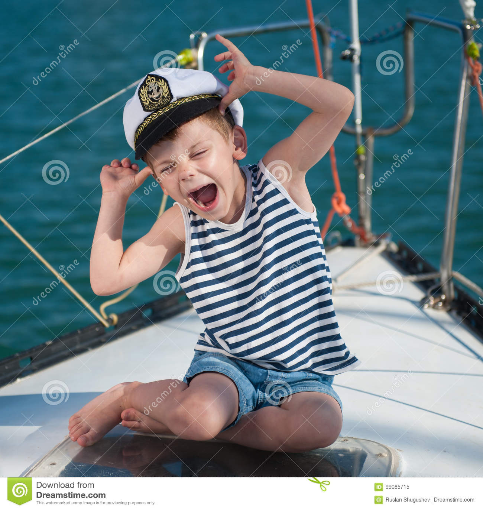 坐豪华小船的滑稽的小男孩佩带的上尉帽子