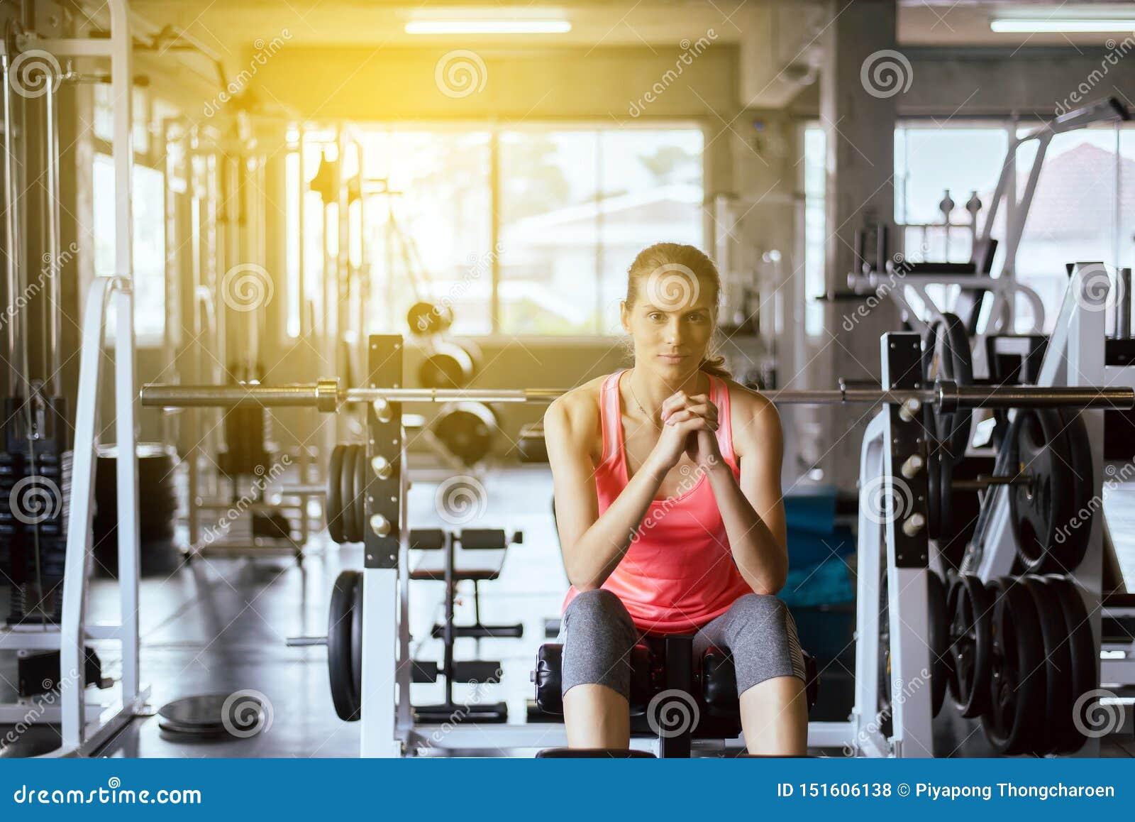 坐适合的妇女和在健身房的健康训练的概念和生活方式以后放松,女性休假在锻炼a以后