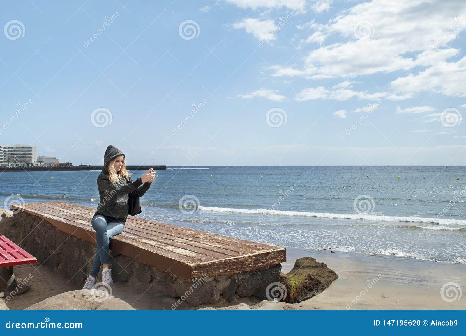 坐长凳和拍摄与后边她的海岸的电话的可爱的白种人妇女照片