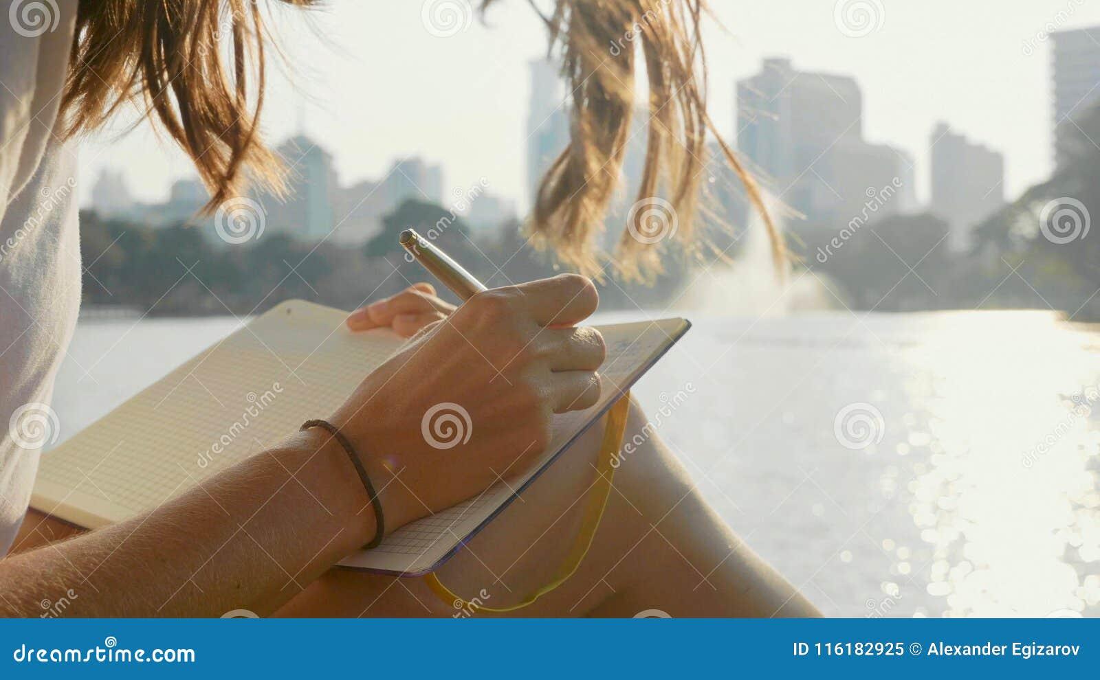 坐长凳在公园和写在日志,特写镜头的少妇