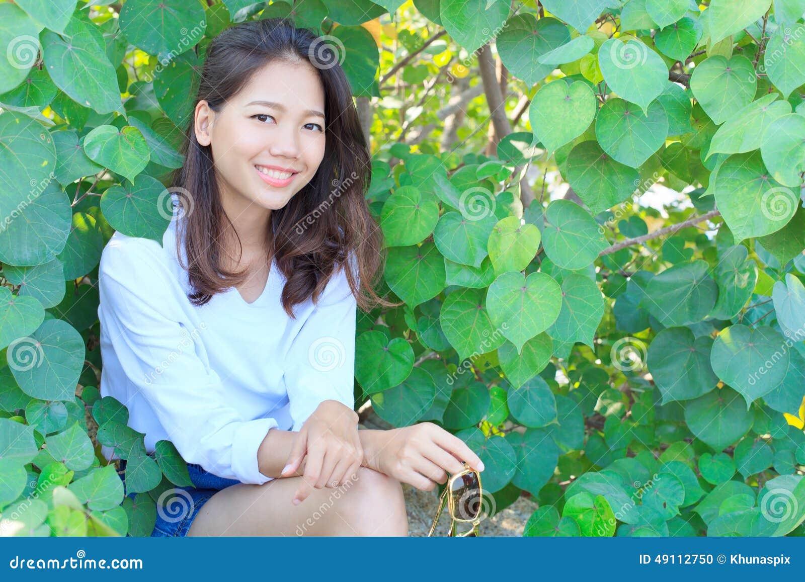 坐以绿色的俏丽的妇女画象离开灌木和smilin