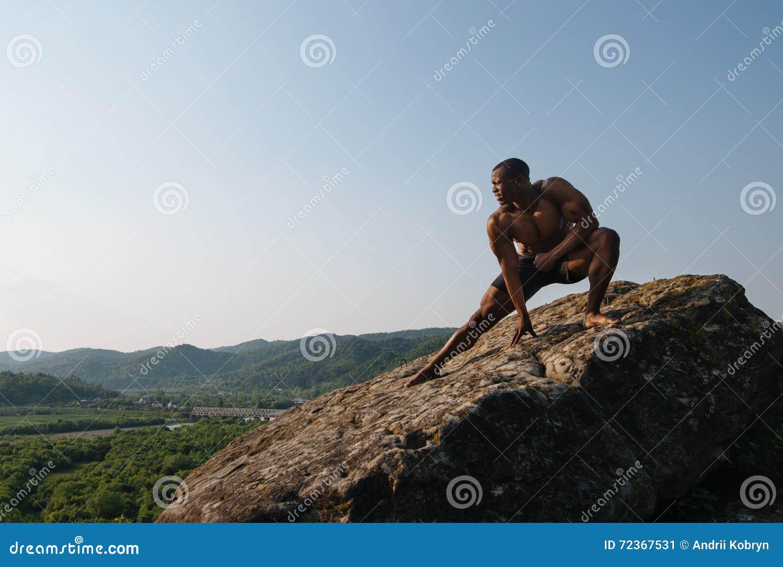 坚强的英俊的非裔美国人的爱好健美者在山的岩石训练 绿色森林山背景