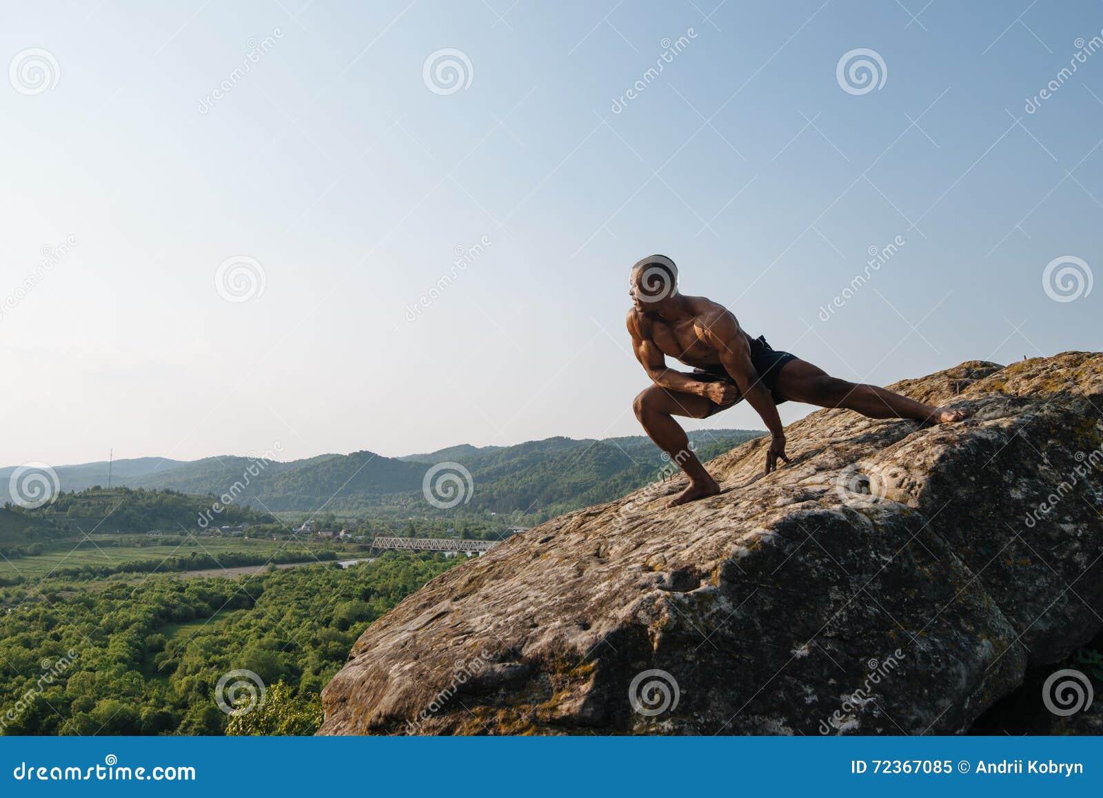 坚强的非裔美国人的爱好健美者在山的岩石训练 绿色森林山背景