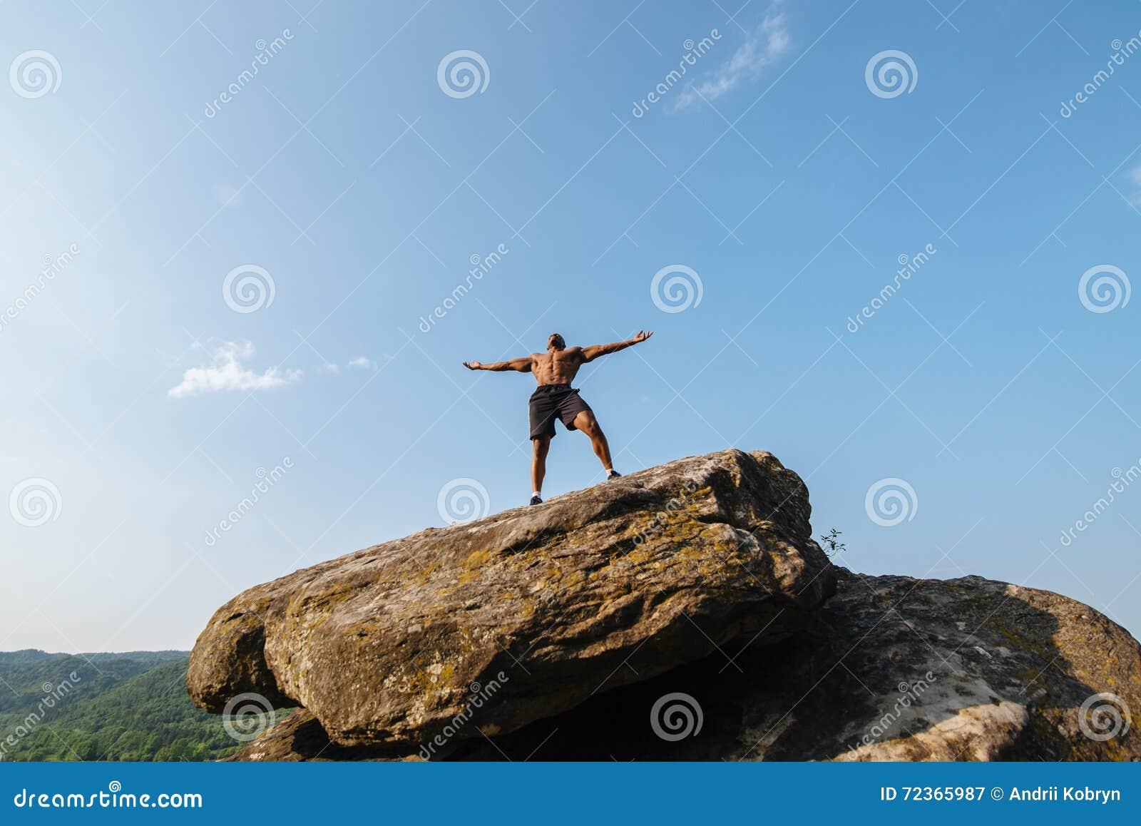 坚强的黑人爱好健美者画象有摆在岩石的赤裸躯干的 蓝色多云天空背景