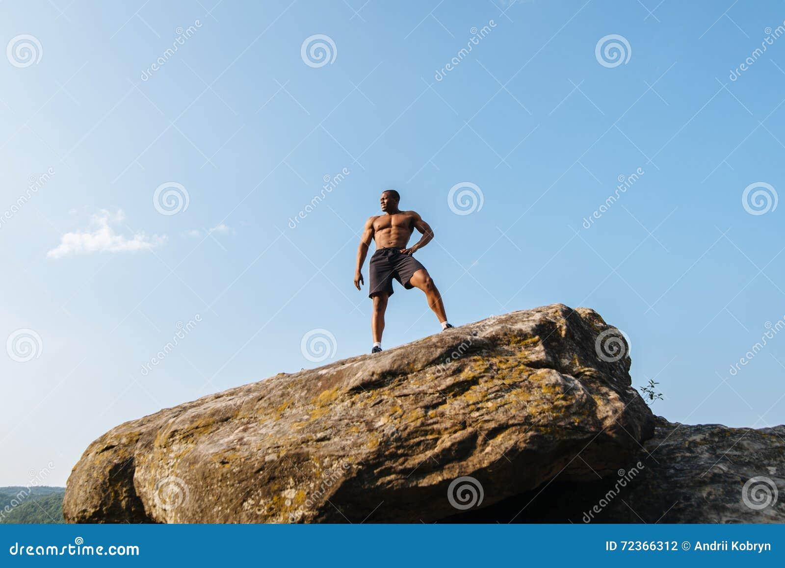 坚强的黑人非裔美国人的人爱好健美者画象有摆在岩石的赤裸躯干的 蓝色多云天空