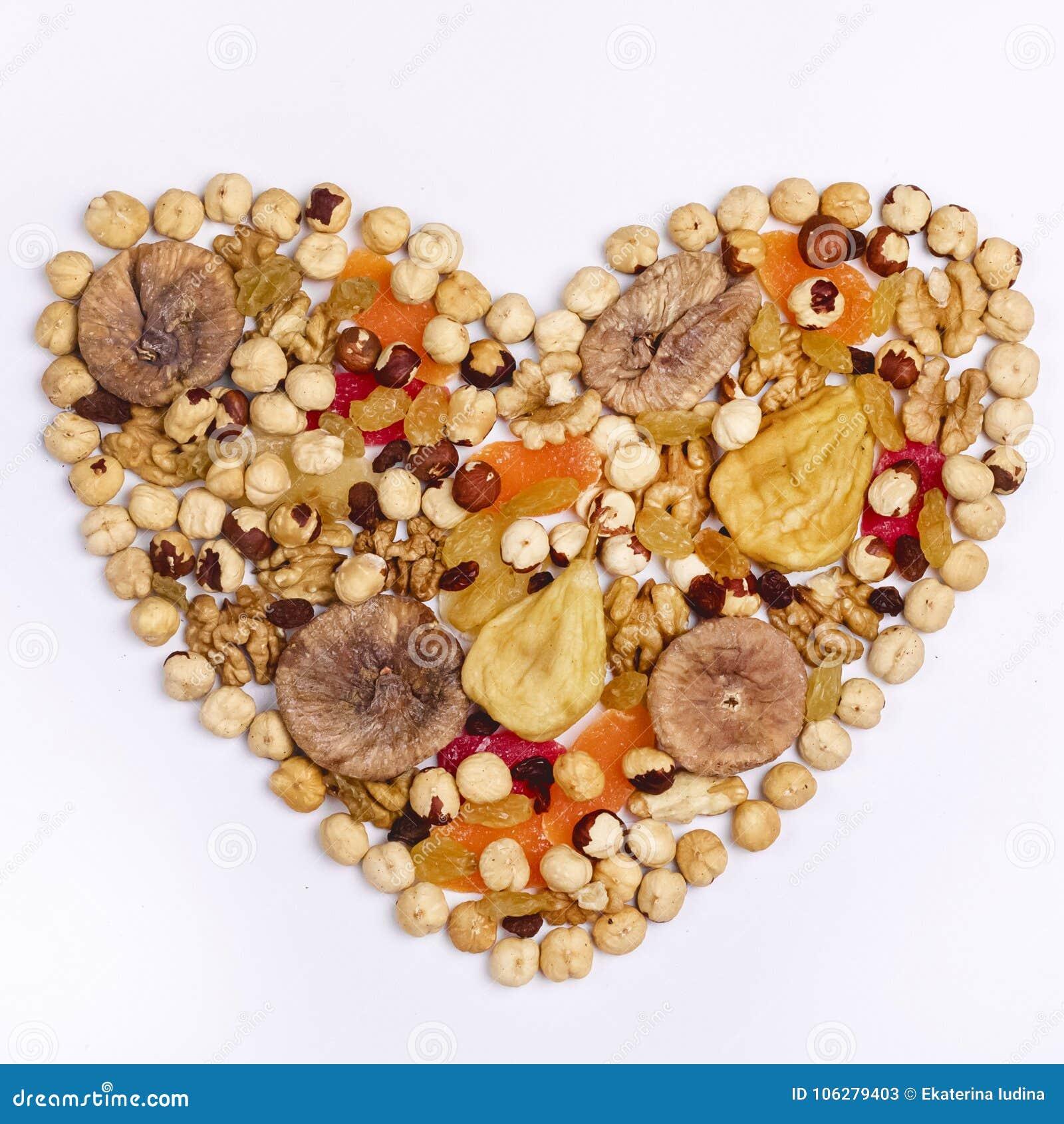 坚果混合和干果子在心脏形状在白色背景顶视图正方形