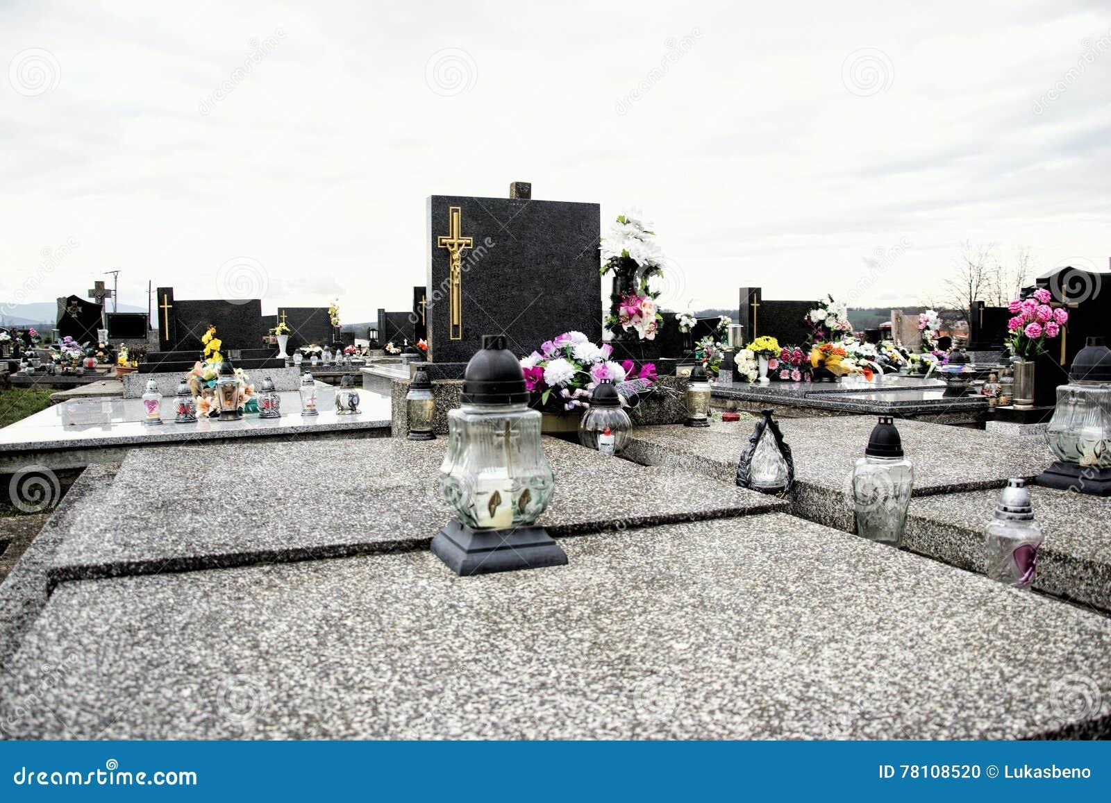 坟墓、墓碑和耶稣受难象在传统公墓 奉献的蜡烛灯笼和花在坟茔石头在坟园