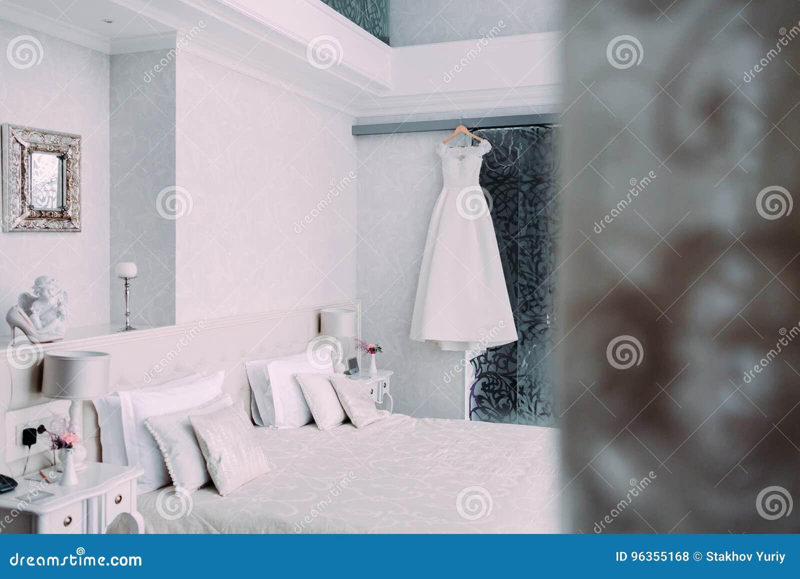 垂悬在一个木挂衣架的白色典雅的新娘礼服在最低纲领派样式的豪华旅馆室