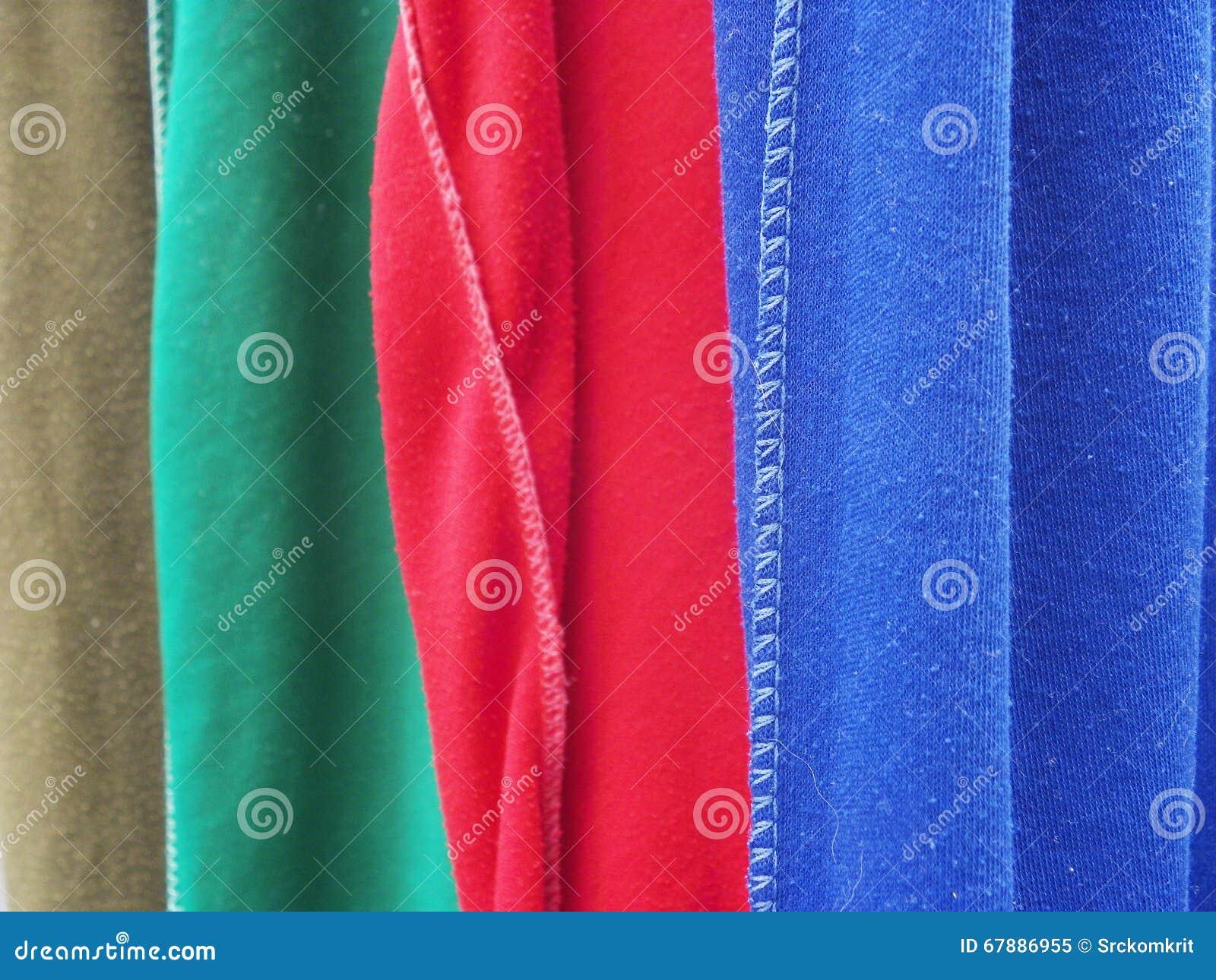 垂悬在挂衣架的五颜六色的行T恤杉行