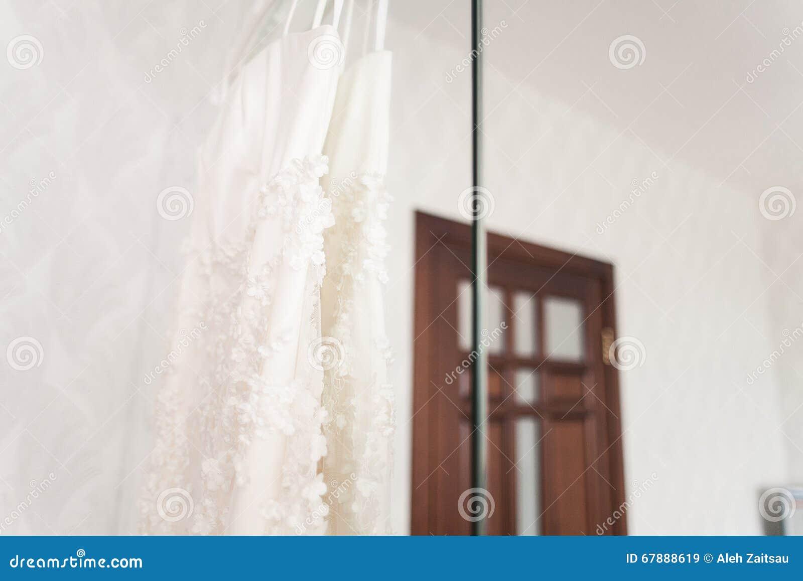 垂悬在色泽的婚礼礼服在旅馆客房