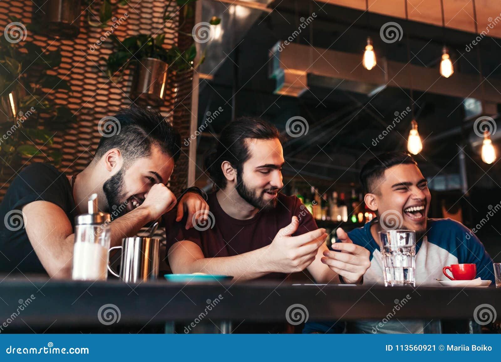 垂悬在顶楼咖啡馆的愉快的阿拉伯年轻人 小组混合的族种人获得乐趣在休息室酒吧