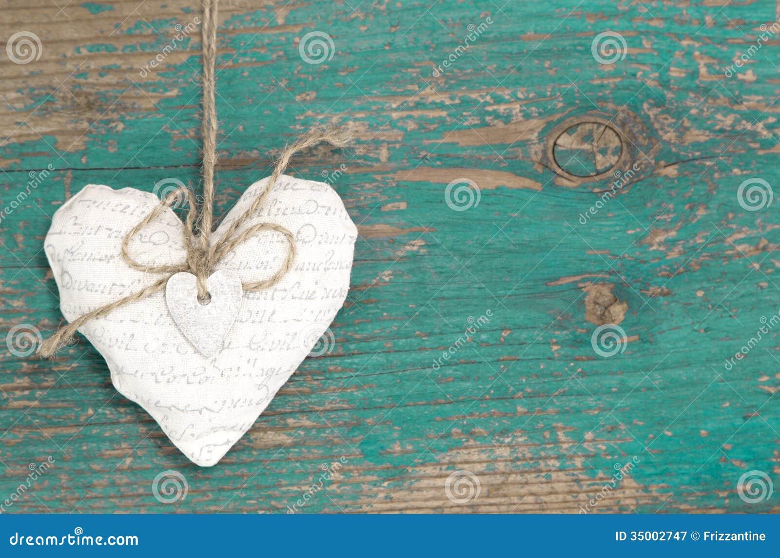 垂悬的心脏和绿松石木背景在乡村模式。