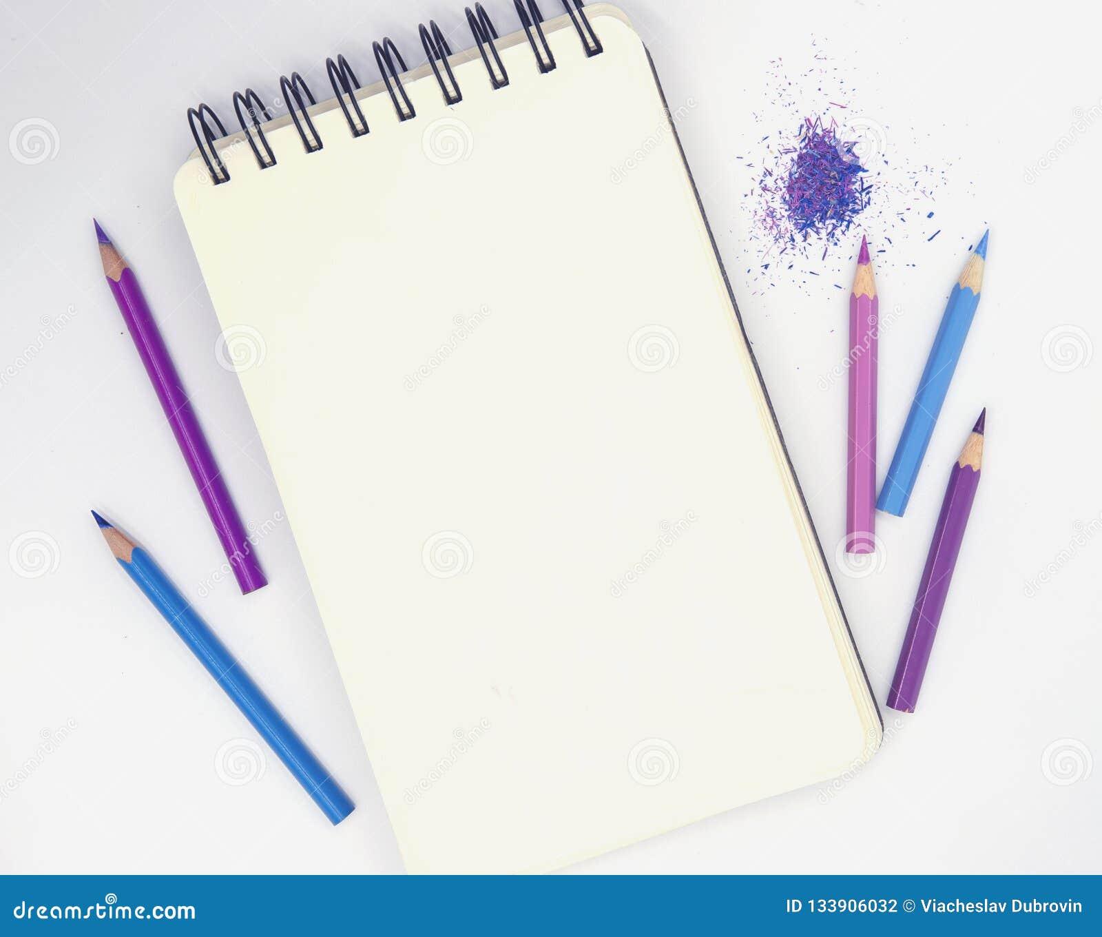 垂直的写生簿和桃红色紫罗兰色铅笔在白色背景 艺术性的台式视图照片