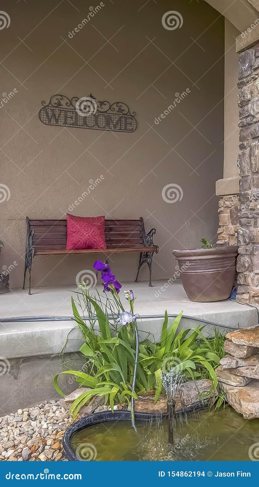 垂直的庭院植物和装饰岩石围拢的池塘和小喷泉