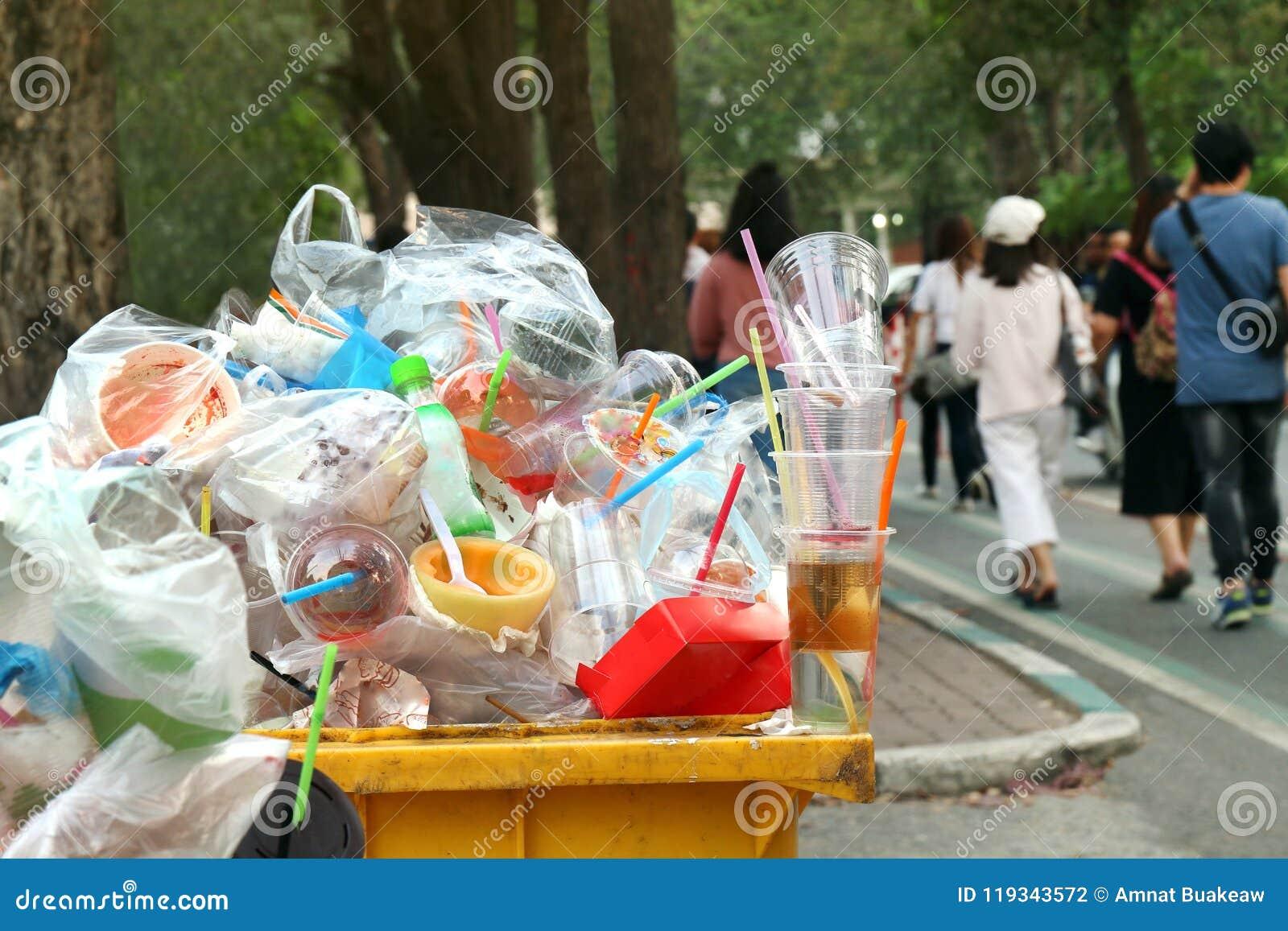 垃圾塑料充分废物垃圾垃圾桶黄色和背景人在边路庭院,垃圾桶,垃圾走