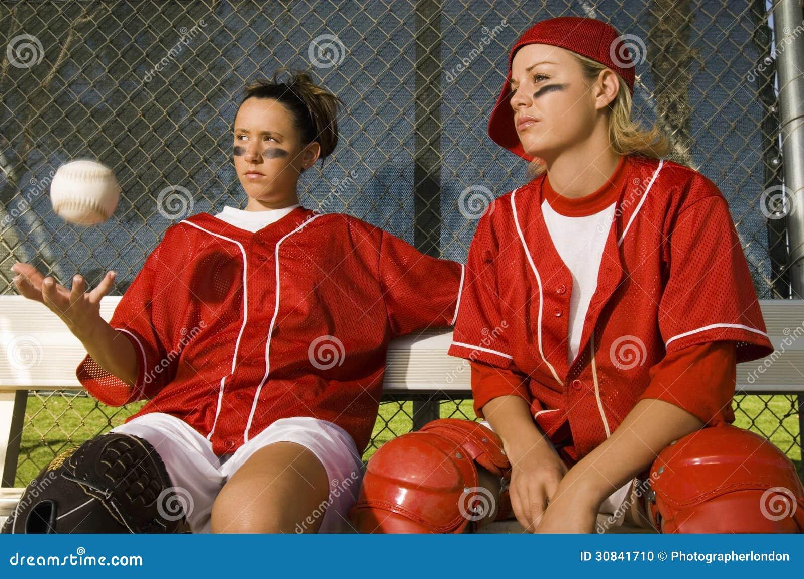 垒球确信的两个运动员坐在独木舟的长凳.高尔夫球包通电话图片