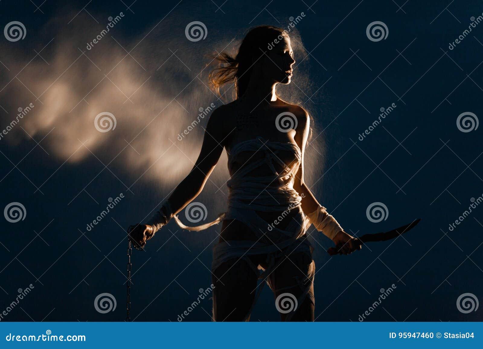 埃及妈咪的图象的女孩站立与金属链子和刀子在她的手上