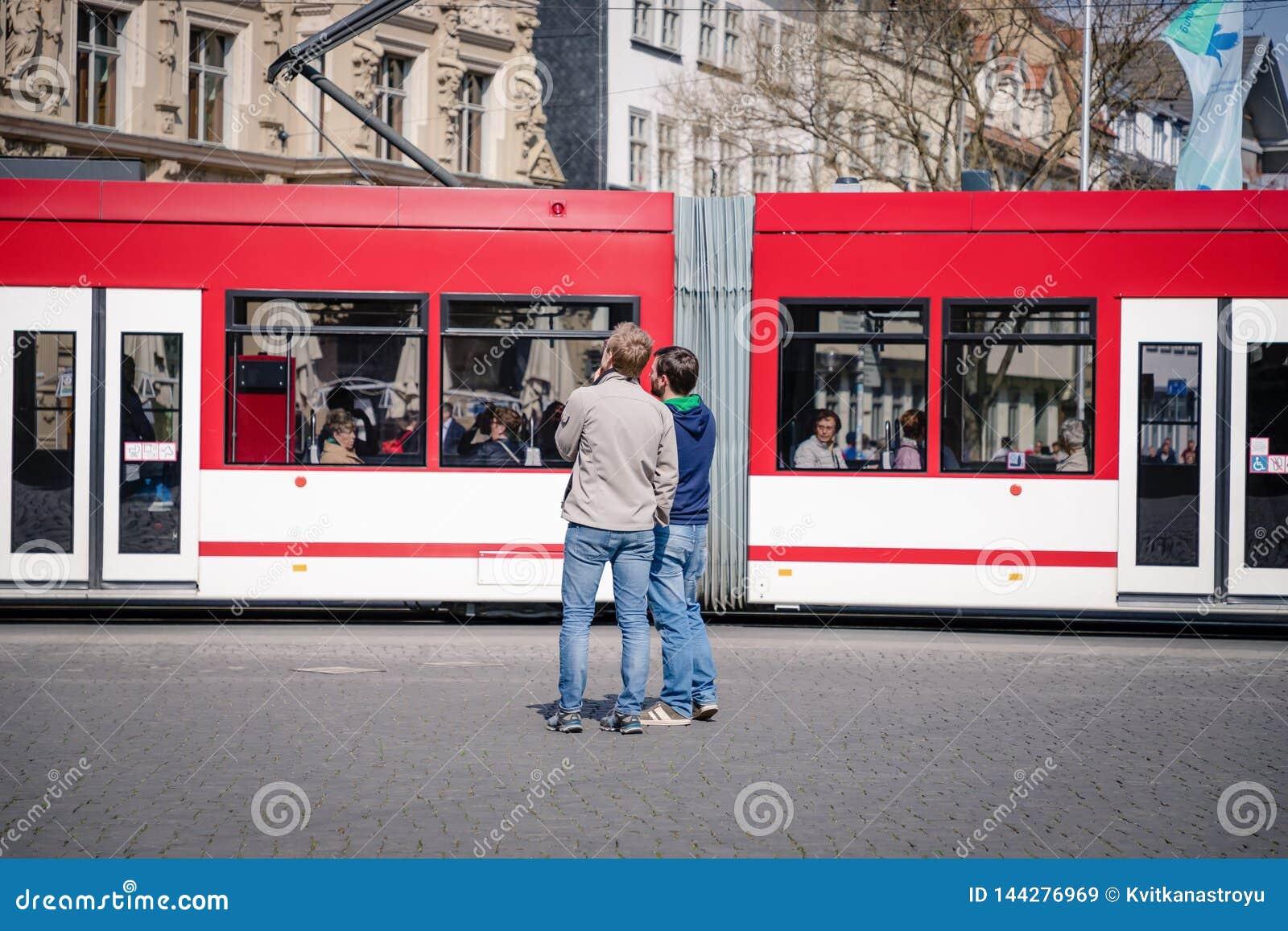 埃福特,德国 2019年4月7日 两偶然年轻人在红色电车背景的市中心