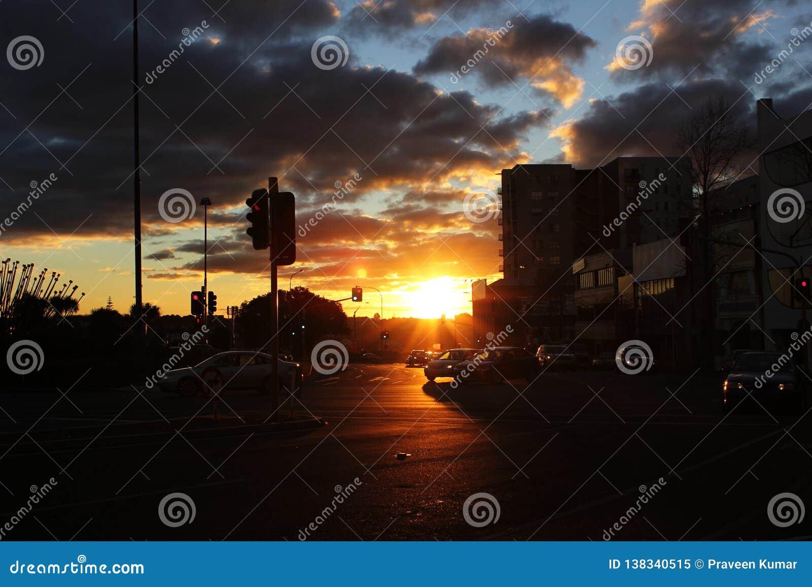 城市日落在与汽车的一阴天在交通信号juction