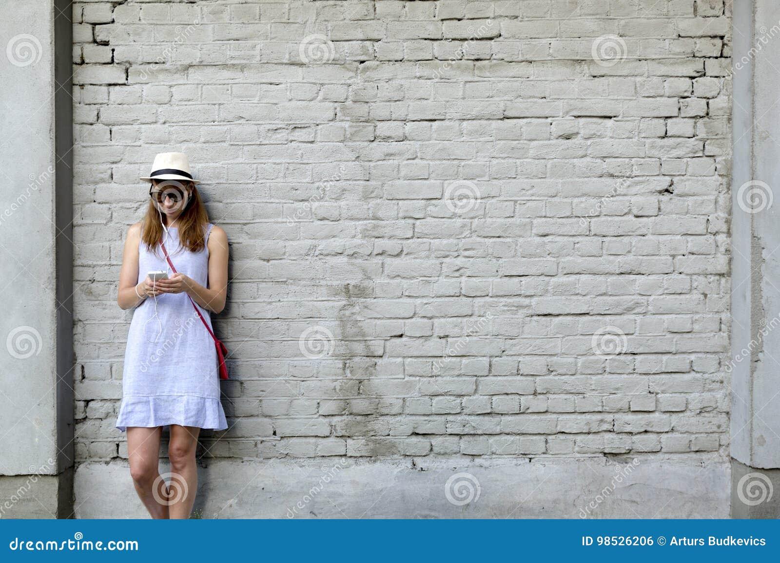 城市生活概念 站立在白色砖墙旁边的少妇听到在耳机的音乐