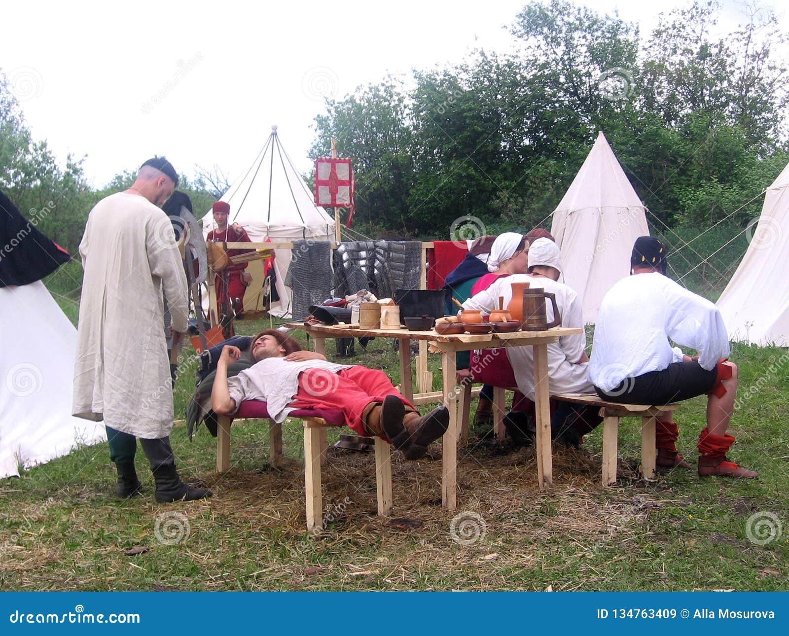 基于地面的中世纪服装的人骑士在帐篷附近在北欧海盗的争斗前