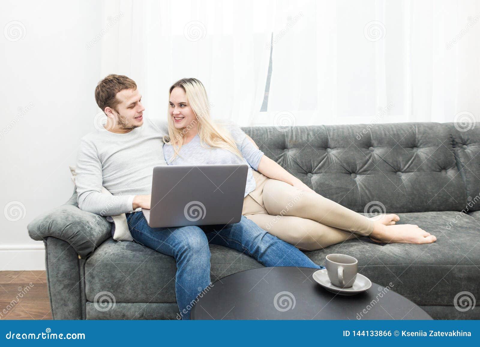 基于长沙发和观看的网上录影的年轻美好的夫妇从一台膝上型计算机在客厅