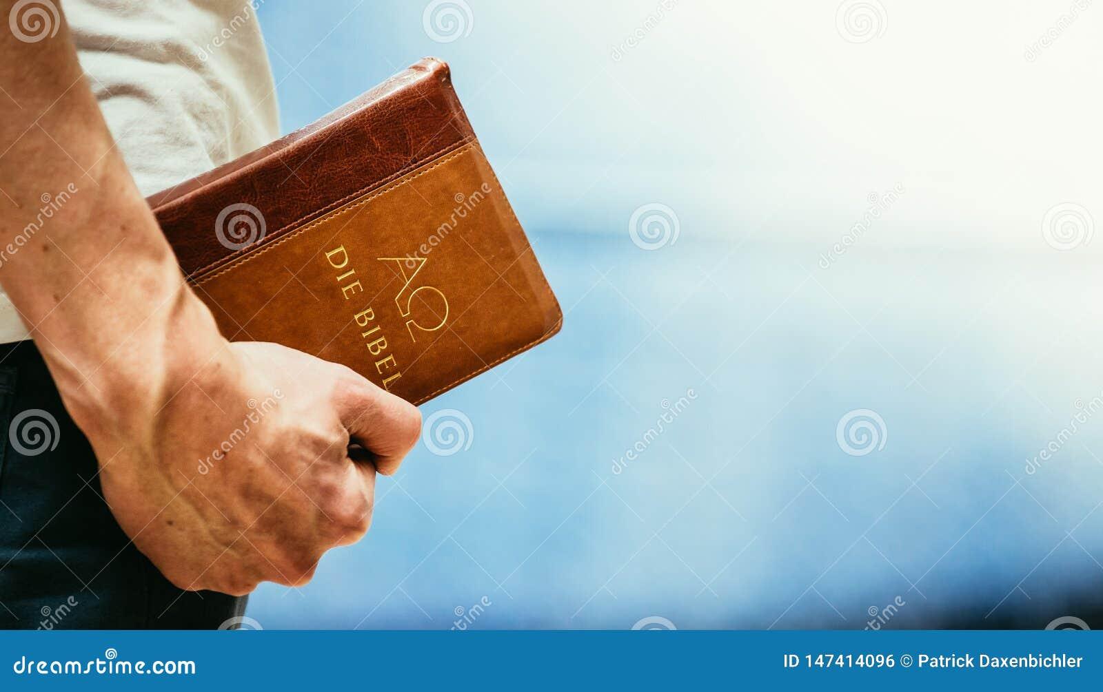 基督徒传教者:年轻人拿着圣经,祈祷