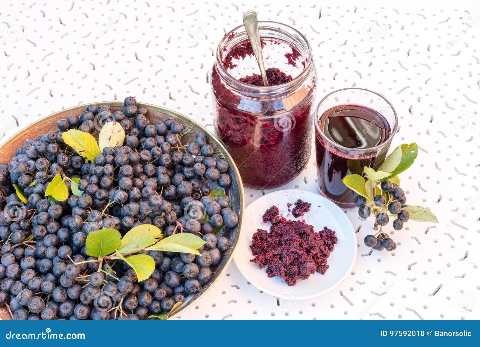黑堂梨属灌木Aronia melanocarpa新鲜的汁液和果酱在玻璃和莓果的在白色织地不很细背景的罐