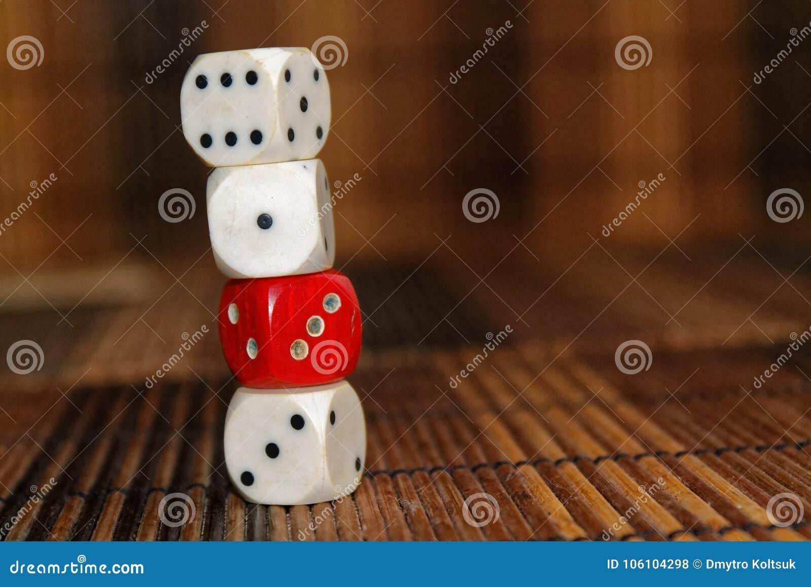 堆三白色塑料切成小方块和在棕色木板背景的一个红色模子 与黑小点的六个边立方体 第1, 3,