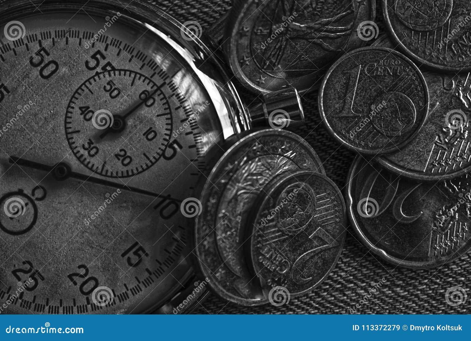 堆与老葡萄酒秒表的欧洲硬币在破旧的老牛仔裤背景