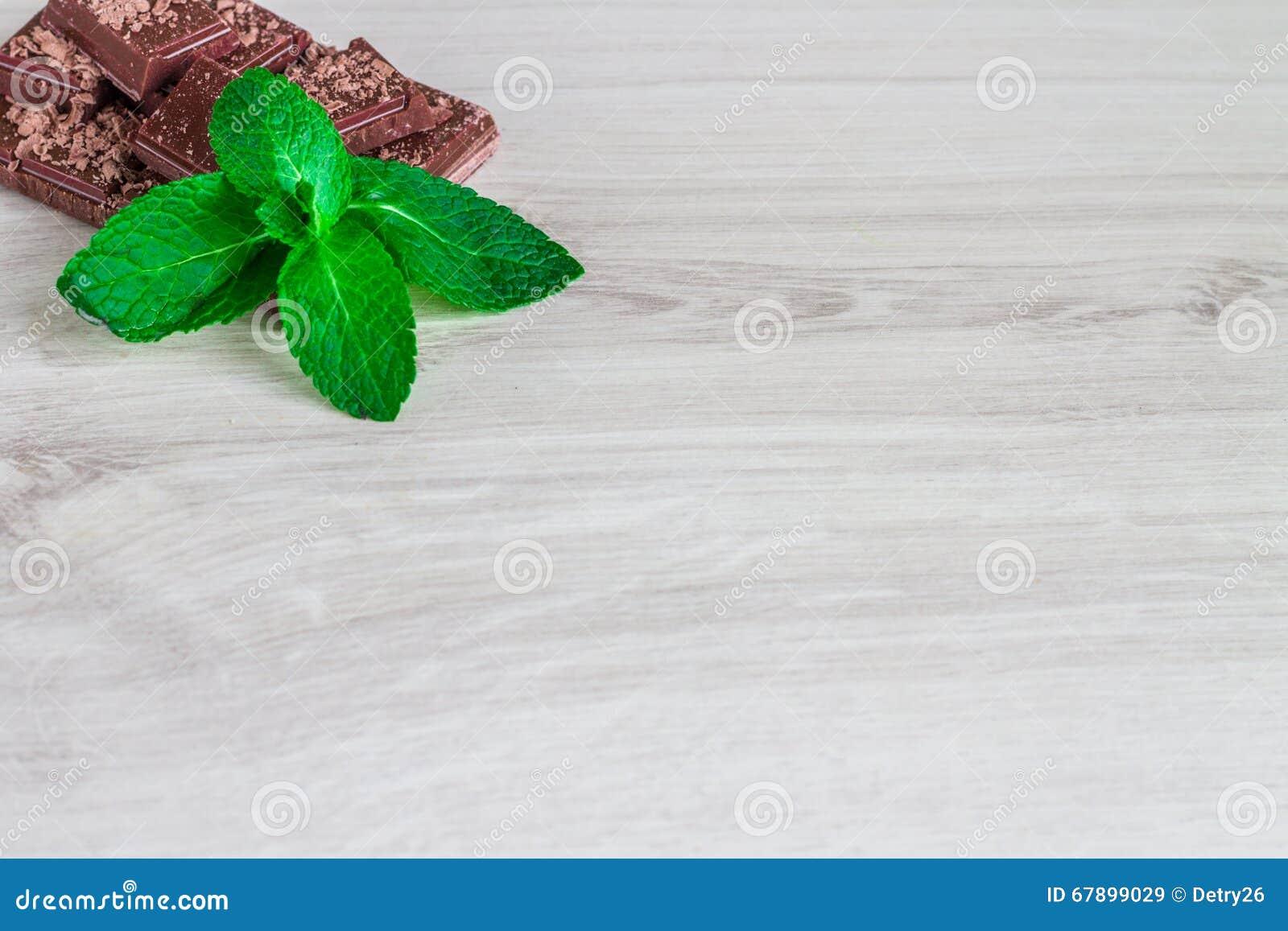 堆与薄荷的叶子的巧克力切片在一张木桌上
